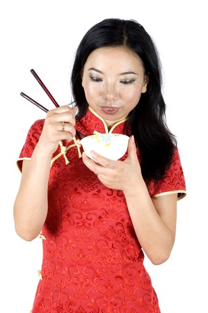 Chinese girl in traditional dress - QiPao, eating food by chopsticks, Chinese New Year in Shanghai, China. photo