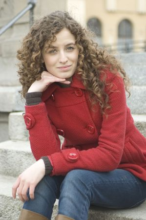 Teenage girl in Poland, portrait. Young girl with curly hairs wearing red coat, posing in Wroclaw city.  photo