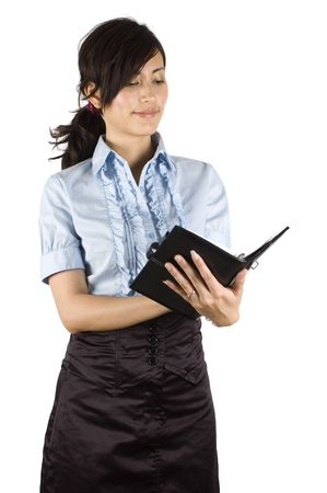 Chinese office lady, elegant clerk. Young Asian girl with kind face expression. Holding pen and notebook, reading and making notes. photo
