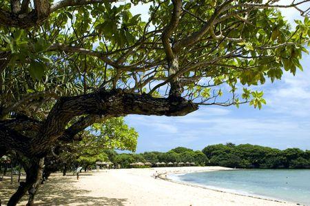 Beautiful Nusa Dua beach, Bali Island, Indonesia. Blue ocean and wide beach with yellow sand.