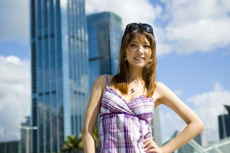 Fashionable Chinese girl in the city. Young female model, pretty Asian girl, fashionable and confident with modern skyscrapers as background. Stock Photo