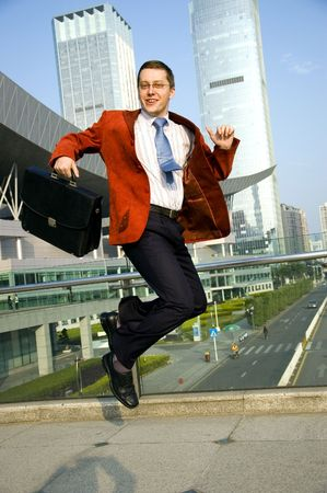Happy, successful businessman - jumping. Wearing red suit and blue tie. Modern skyscrapers as background. photo