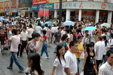 CHINA, SHENZHEN - JULY 30, 2006: crowd of people shopping in city center. 新聞圖片