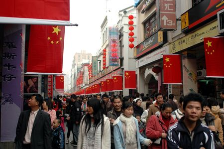CHINA, SHENZHEN - FEBRUARY 8, 2008: Chinese people shopping and gathering in city center. Chinese New Year - streets decorated with national flags.