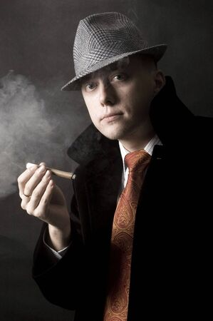 Young European gentleman with elegant clothes, tie and coat, wearing stylish hat. Smoking cigar. photo