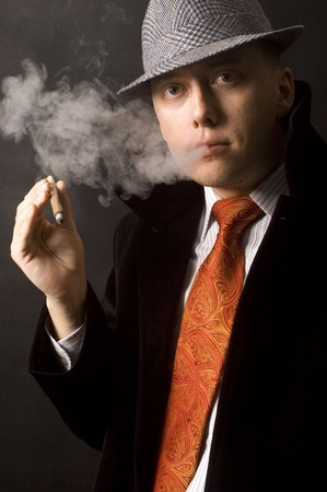 Handsome businessman with hat, coat and red tie. Seus face expression, smoking cigar. Stock Photo - 7618352