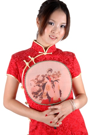 Chinese model in traditional dress called QiPao, holding fan. Asian cute girl, young model with friendly and happy face expression. Stock Photo - 8471769