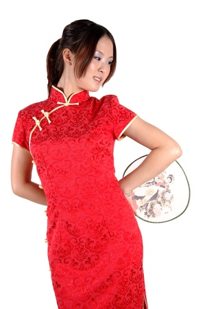 Chinese model in traditional dress called QiPao, holding fan. Asian cute girl, young model with friendly and happy face expression. Stock Photo - 8471765