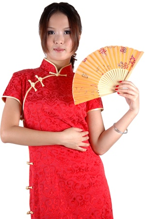 Chinese model in traditional dress called QiPao, holding fan. Asian cute girl, young model with friendly and happy face expression. Stock Photo - 8471762