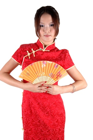 Chinese model in traditional dress called QiPao, holding fan. Asian cute girl, young model with friendly and happy face expression. Stock Photo - 8471763