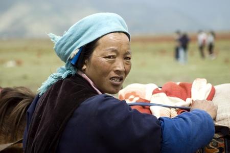 CHINA, YUNNAN PROVINCE, SHANGRILA TOWN - SEPTEMBER 13: Naxi minority, woman renting horses to tourists who visit Sino-Tibetan mountains. Editorial