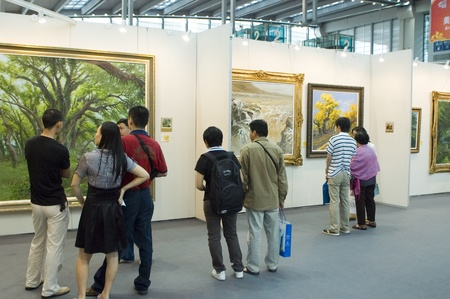 CHINA, GUANGDONG, SHENZHEN - MAY 16, 2009: China International Cultural Industries Fair, visitors watching modern and ancient art, Chinese paintings and graphics made in ink.