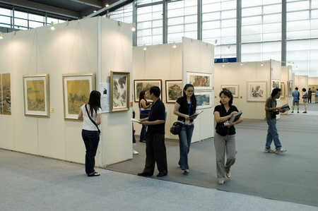 art gallery: CHINA, GUANGDONG, SHENZHEN - MAY 16, 2009: China International Cultural Industries Fair, visitors watching modern and ancient art, Chinese paintings and graphics made in ink.