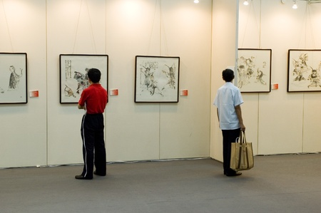exhibit: CHINA, GUANGDONG, SHENZHEN - MAY 16, 2009: China International Cultural Industries Fair, visitors watching modern and ancient art, Chinese paintings and graphics made in ink.