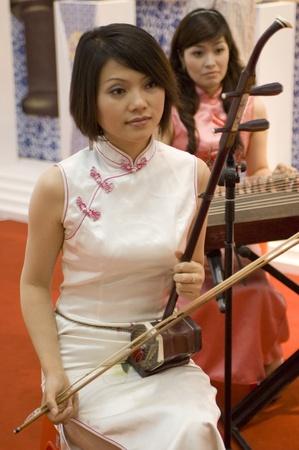chinese opera: CHINA, GUANGDONG, SHENZHEN - MAY 16, 2009: China Culture Exhibition, showing Chinese art, traditions, folk music, costumes, modern art, opera, different minorities. Photo presents Chinese girls, musicians playing traditional instruments.