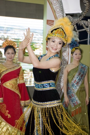 promover: CHINA, GUANGDONG, SHENZHEN - MAY 17, 2009: China Cultural Fair: charming Chinese girls in traditional costumes promote Guangxi province.