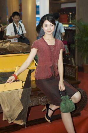 promotes: CHINA, GUANGDONG, SHENZHEN - 17 de mayo de 2009: China Cultural industrias Feria Internacional: joven modelo promueve muebles chinos tradicionales.