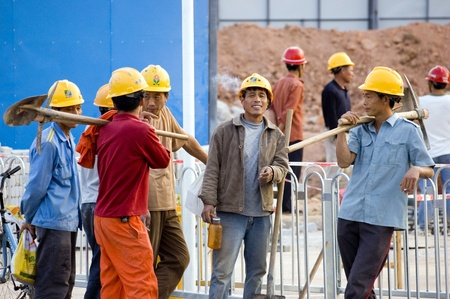 CHINA, SHENZHEN - NOVEMBER 24: Workers from all around China are building Shenzhen metro, group of workers having break for cigarettes on October 24, 2008 in Shenzhen, China.