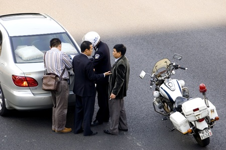 CHINA, SHENZHEN - DECEMBER 9: Policeman resolving car accident in Chinese city, even there are more and more cars in China, driving skills are getting worse, accident on December 9, 2008 in Shenzhen, China.