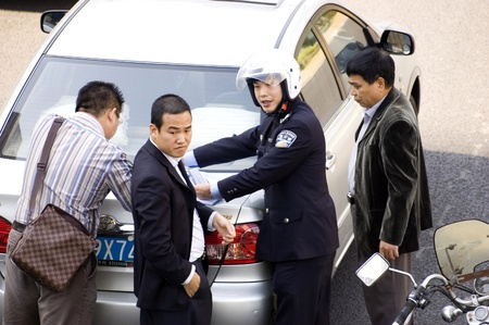 resolving: CHINA, SHENZHEN - DECEMBER 9: Policeman resolving car accident in Chinese city, even there are more and more cars in China, driving skills are getting worse, accident on December 9, 2008 in Shenzhen, China.