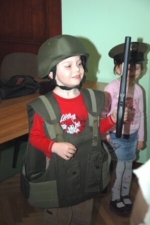 security vest: WROCLAW, POLAND - April 3: Open Day of National Bank of Poland. Small boy tries security guard vest and helmet on April 3, 2011.