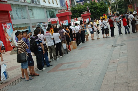 to queue: CHINA, SHENZHEN - AUGUST 20: overpopulated city in Guangdong province. Crowd of people in city center waits in queue and pushes to the buses after work on August 20, 2010. Editorial