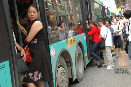 CHINA, SHENZHEN - AUGUST 20: overpopulated city in Guangdong province. Crowd of people in city center waits in queue and pushes to the buses after work on August 20, 2010. Editorial