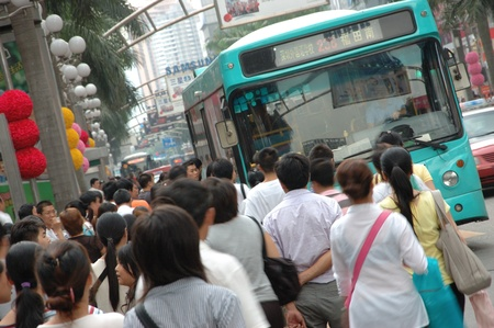 CHINA, SHENZHEN - AUGUST 20: overpopulated city in Guangdong province. Crowd of people in city center waits in queue and pushes to the buses after work on August 20, 2010. 新聞圖片
