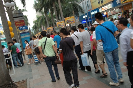 CHINA, SHENZHEN - AUGUST 20: overpopulated city in Guangdong province. Crowd of people in city center waits in queue and pushes to the buses after work on August 20, 2010. Publikacyjne