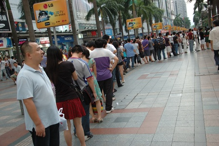 CHINA, SHENZHEN - AUGUST 20: overpopulated city in Guangdong province. Crowd of people in city center waits in queue and pushes to the buses after work on August 20, 2010. Redakční