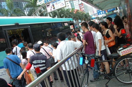 CHINA, SHENZHEN - AUGUST 20: overpopulated city in Guangdong province. Crowd of people in city center waits in queue and pushes to the buses after work on August 20, 2010. Zdjęcie Seryjne - 9350427
