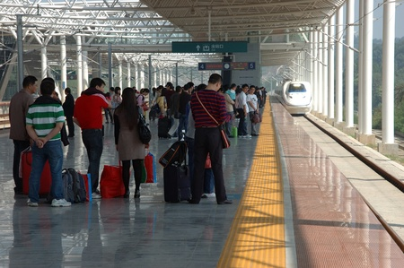 YUEYANG - HUNAN, CHINA - OCTOBER 3: China invests in fast and modern railway, trains with speed over 340 kmh. Passengers wait for train to Guangzhou on October 3, 2010 in YueYang station.