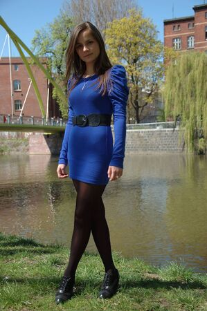 black stockings: Sweet, young girl portrait. Teenage model in Poland wearing casual blue dress and black stockings, smiling gently. Stock Photo