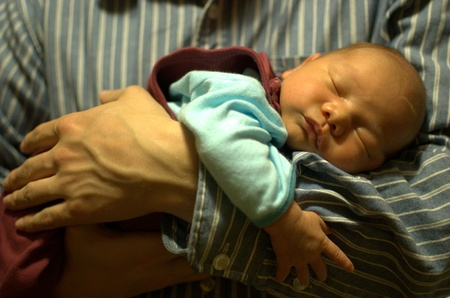 Infant sleeping in hands of his father  Small baby feels relaxed and guarded by parent