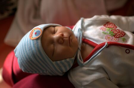 Infant wearing cap  Little boy is sleeping peacefully on mom Stock Photo - 13901185