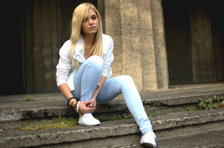 Young female model wears casual clothes. Sits on stairs with natural face expression, teenage girl cool and relaxed.