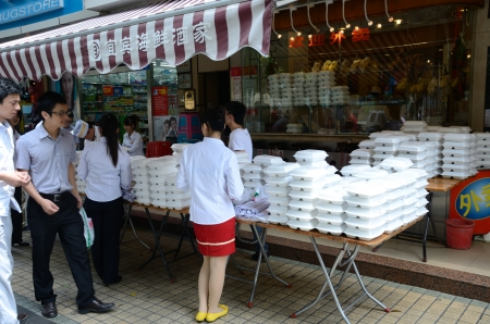 futian: SHENZHEN, CHINA - SEPTEMBER 6:  Unidentified waitress and chefs prepare lunch boxes for office workers in Futian area on September 6, 2012. Editorial