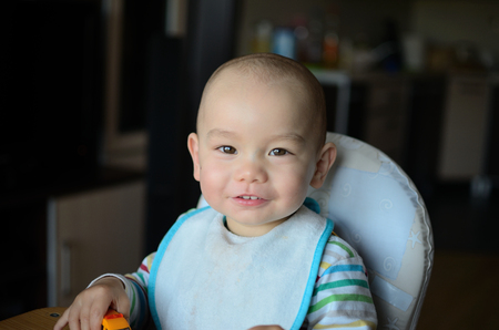 Cute baby boy sits peacefully in feeding-chair. Portrait of twenty months old boy. photo