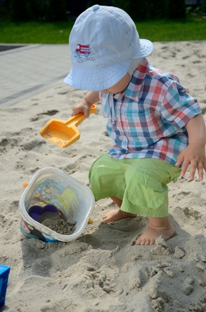sandpit: One and half year old baby boy playing in sandpit. Baby wears simple hat, shirt. Boy holds shovel and plays with the sand.