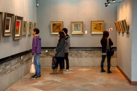 admires: CANTON, CHINA - MARCH 8, 2011: Unidentified person admires Chinese paintings inside Chen Clan Ancestral Hall on 8th March in Guangzhou, China. Editorial