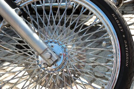 spokes: Closeup photo of motorcycle wheel with shiny spokes and metallic rim.