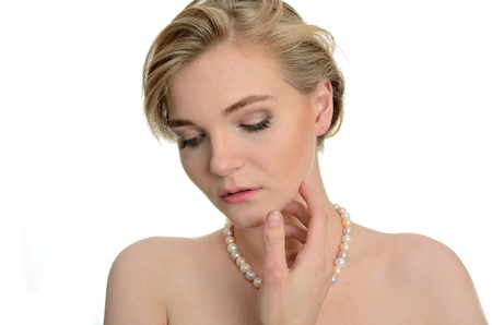 one of a kind: Model with soft face expression. Kind girl wears pearl on her neck, one hand near face.