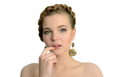 Female model with earrings. Young girl with blond hairs, holding finger near her lips.