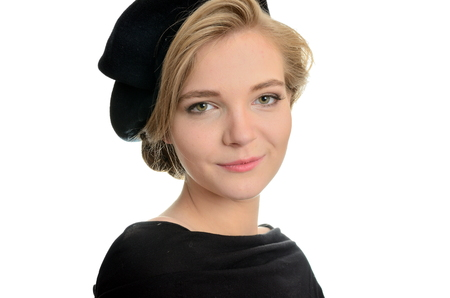 Elegant female model with kind face expression. Young girl with blond hairs, wearing black top and black beret.