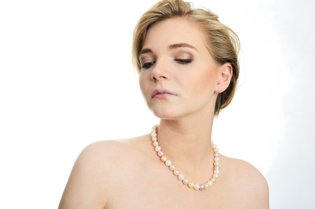 peacefull: Beautiful female model with pearls on her neck. Portrait of young girl with soft and kind face expression.