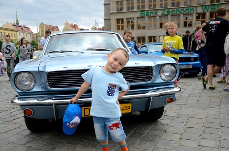 bewonderen: WROCLAW, POLAND - JULY 29: Kids admire Mustang car. Around fifty different cars mostly from Poland and Germany gathered for Mustang Race 2015 on 29 July 2015  in Wroclaw, Poland.