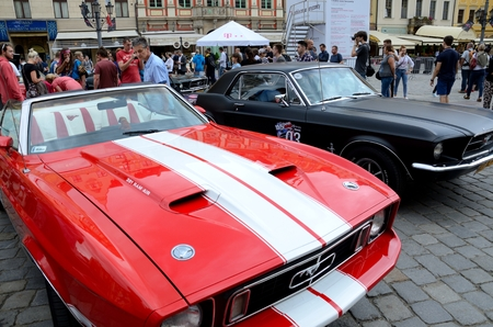 admire: WROCLAW, POLAND - JULY 29: People admire classic Mustang. Around fifty different cars mostly from Poland and Germany gathered for Mustang Race 2015 on 29 July 2015  in Wroclaw, Poland.
