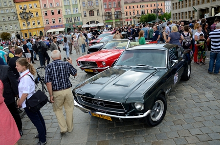 bewonderen: WROCLAW, POLAND - JULY 29: People admire classic Mustang. Around fifty different cars mostly from Poland and Germany gathered for Mustang Race 2015 on 29 July 2015  in Wroclaw, Poland.