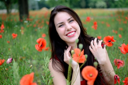 polish girl: Beautiful polish girl surrounded by field full of poppies. Young female model with charming smile, wearing red dress. Stock Photo