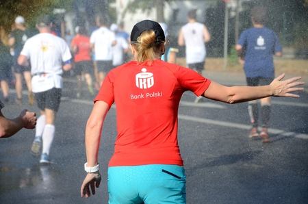 challange: WROCLAW, POLAND - SEPTEMBER 13: Unidentified runner cooling his body with cold water during PKO Marathon Wroclaw 2015 on 13th September 2015  in Wroclaw, Poland.